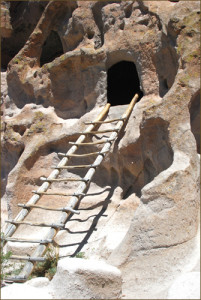 Wooden ladder leading to desert cave's entrance.