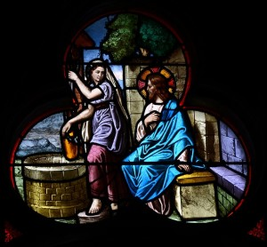A stained glass picture of the woman at the well with Jesus.
