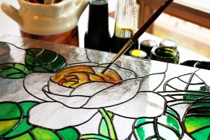 A paintbrush adding yellow paint to a clear stained glass rose.