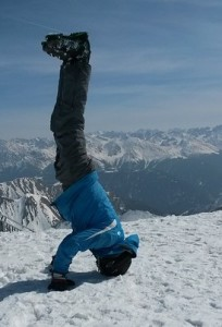 Skier with ski boots on, doing a headstand in the snow.