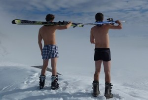 Two male skiers wearing only shorts and ski boots, contemplate a snowy slope. Their snowboard and skis are carried on their shoulders.