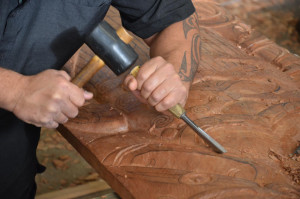 Woodworker carving out a design with a mallet and chisel.