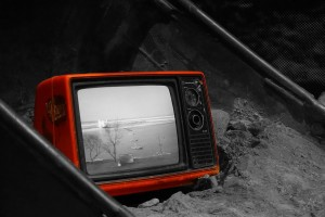 An old, red TV in a grey, ash-filled bin with a black and white picture playing.