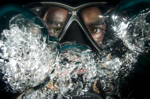 Close-up of scuba diver's face under water, blowing air bubbles and obscuring his mask.