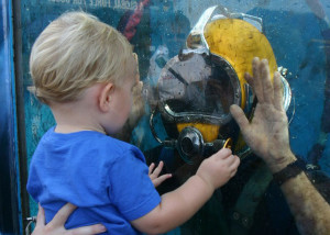 A toddler looking into a tank is face to face with a diver, who greets him.