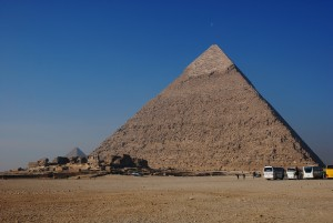 A large pyramid in Egypt with 3 tiny tour buses parked in front.