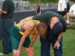 A teenage track athlete bent over after the race, with his coach encouraging him.