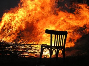 An empty chair before a forest fire.
