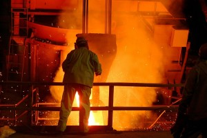 Man overseeing molten metal in a steel mill.