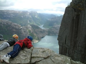 Two boys, laying face-down on a rock ledge, looking at a fjord in Norway.