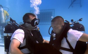 Student in a pool being trained to breathe underwater by a diving instructor.