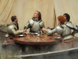 Four medieval knights sitting around a table in armor, drinking.