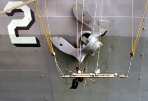 A navy man on a scaffold painting a ship's anchor several times his size.