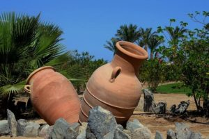 Two large clay jars outside in the sun.
