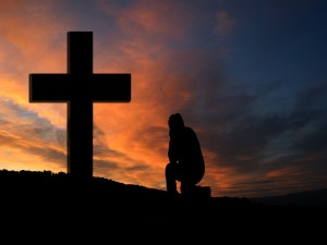 Man kneeling in prayer before an outdoor cross at sunset.