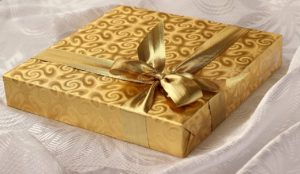 Gold wrapped Christmas gift with a golden bow and ribbon.