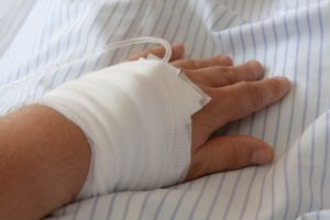 Resting hand wrapped in gauze bandages with an IV tube inserted.