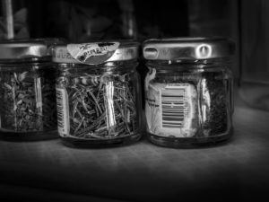 Black and white image of baby jars re-used.