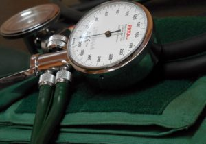 Close-up of green blood pressure cuff, dial and stethoscope.