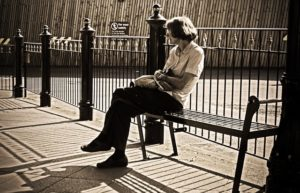 Woman waiting on a metal bench.