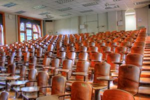 Empty chairs in a large college lecture hall.