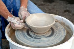 Potter shapes a clay bowl on the wheel.