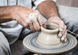 The potter's hands shape the clay on the wheel.