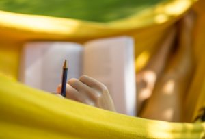 Female student studying while stretched out in a yellow hammock.