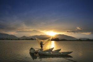 A Vietnamese fisherman using his net at sunset.