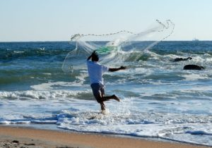 A fisherman in the surf, casting a net.