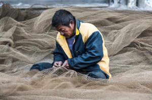 A fisherman repairing his nets..