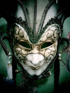 A disturbing green costumed harlequin in gold and white make-up.