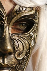 Half a woman's face, in an elaborate gold mask with a single human eye looking out.