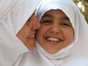 A Muslim mother and daughter in white head scarves.