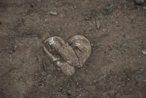 A heart-shaped stone, buried in the dirt.