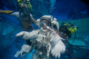 Astronaut under water in his spacesuit, surrounded by two scuba divers.
