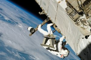 Spacewalking astronaut outside the station, fixing a problem upside down.