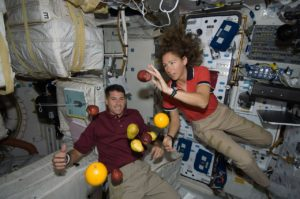 Two astronauts in the space station, demonstrating weightlessness with fruit.