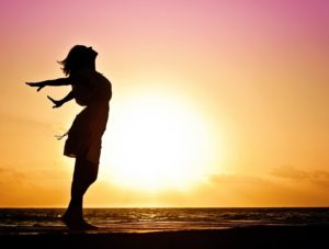 Silouette of a woman standing triumphant on the beach at sunrise.