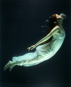 A woman underwater, in a flowing white dress, swims upward toward the surface.