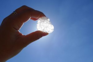 Fingers holding a small ice heart up to the sun in a blue sky.