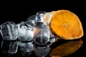 Ice cubes and an orange slice on a black background.
