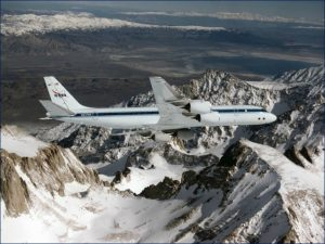 An airplane, NASA's B-737 Flying Laboratory, flies over snow-covered mountains.