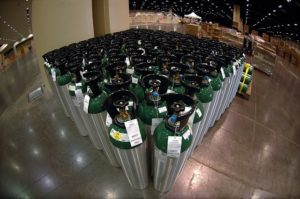 Dozens of oxygen canisters standing beside each other in a warehouse.