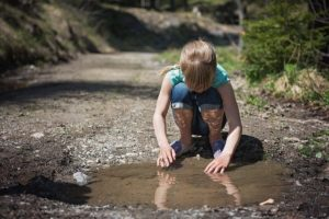 A little girl, gazing in fascination into a mud puddle.
