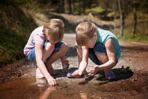 Two little girls, gazing in fascination into a mud puddle.