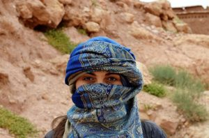 A woman whose face and hair is covered with a blue scarf, standing in desert terrain.