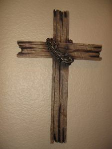 A rough wooden cross with a chain wrapped around it.