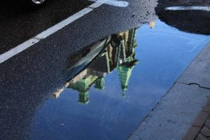 A puddle on an Amsterdam street in Holland, reflecting a church.