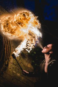 Young woman breathing fire in the darkness.